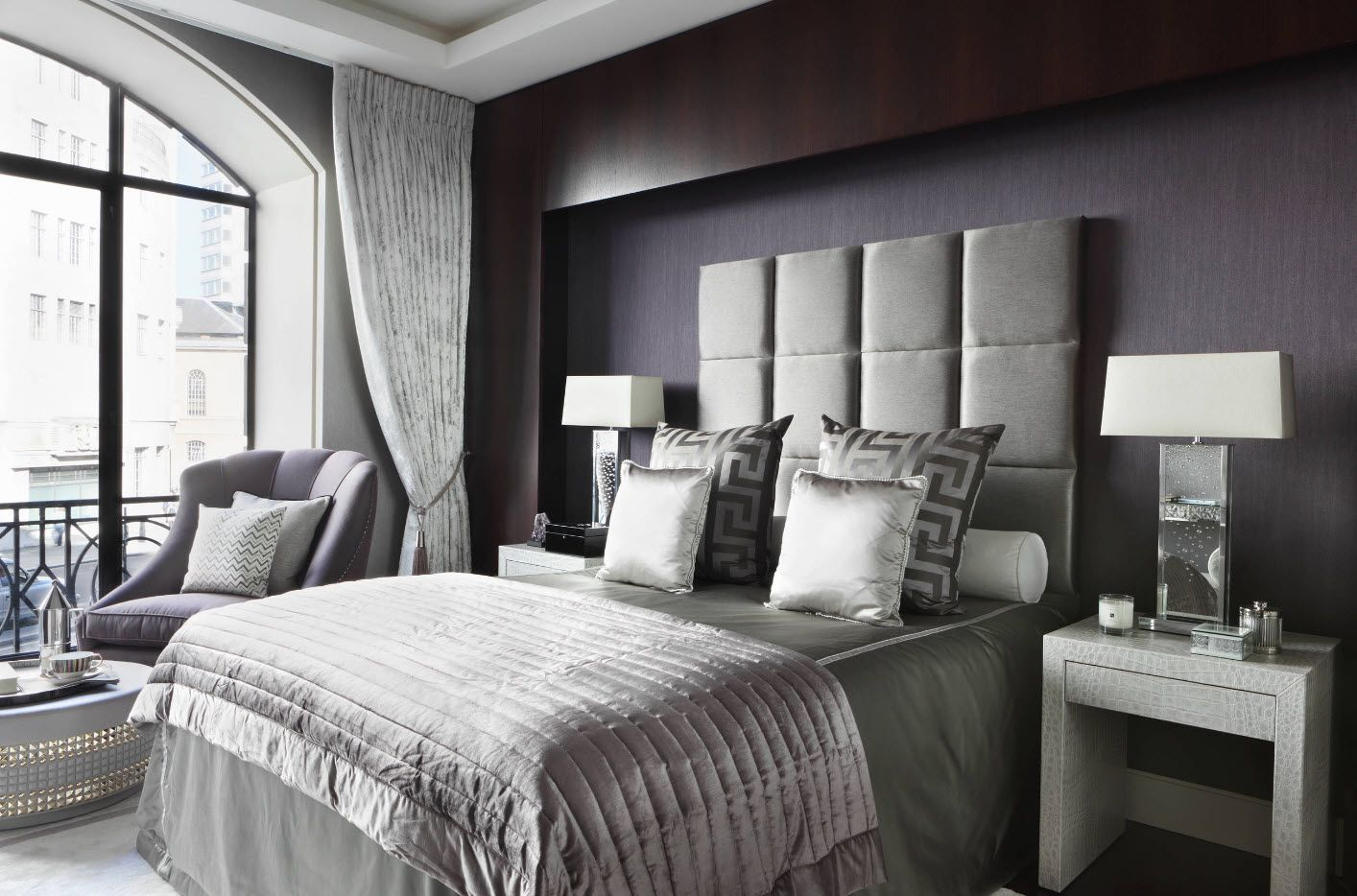 Gray quilted headboard at the modern dark dome of the accent wall