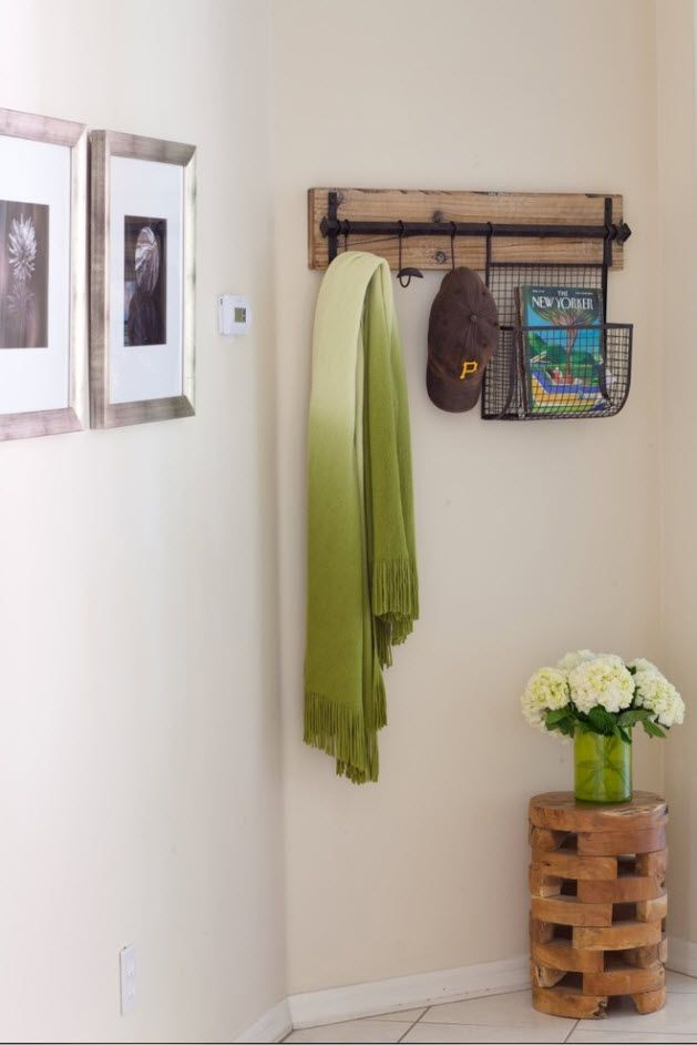 Rustic design of the entrance with wooden hanger and picture frames