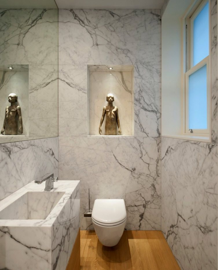 Artificial marble for the walls and wooden trim of the floor in the chic toilet