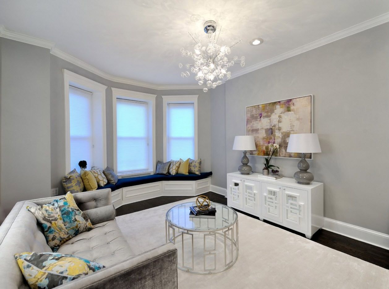 Bay window gray color wall finished living room with cozy white furniture