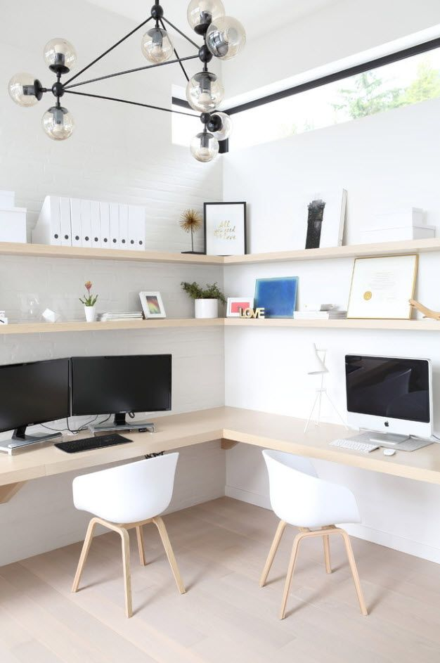 Angle of the room with light wooden shelves and two working places