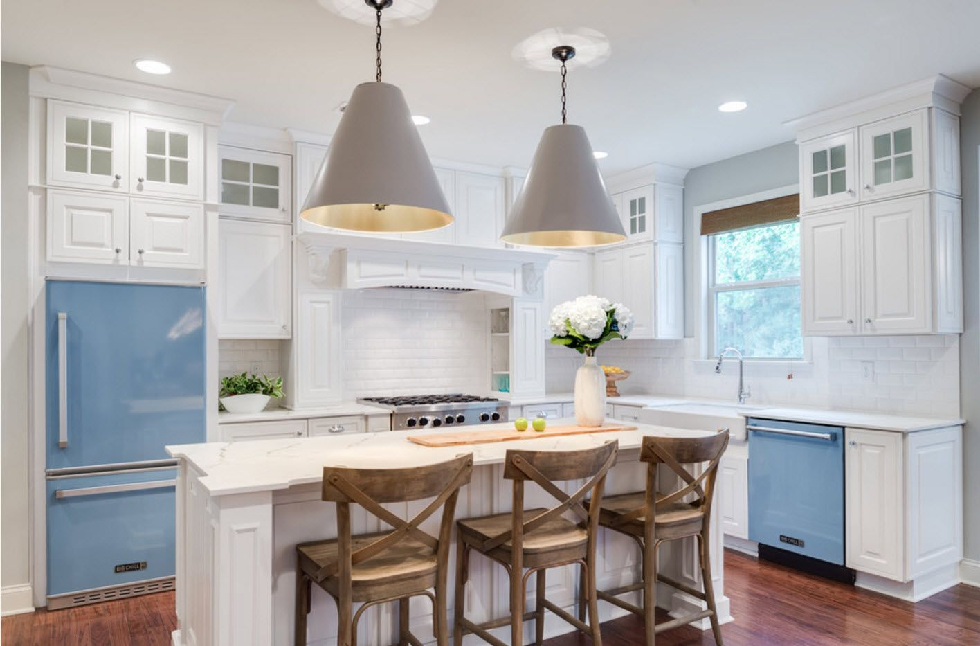 Gray big lampshades over the kitchen island with set of wooden chairs at it