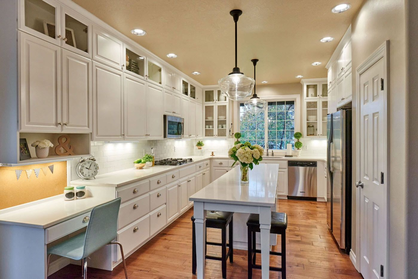 White classic set of the kitchen with white kitchen facades and glossy table in the middle