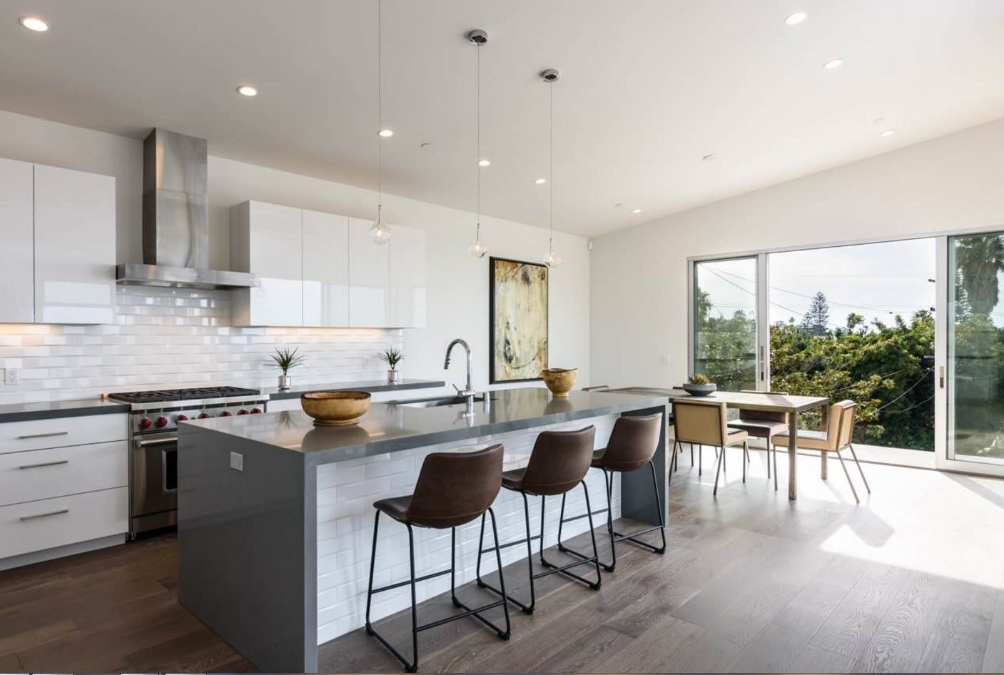 Glossy marble simulating island of the large kitchen with white glossy surfaces