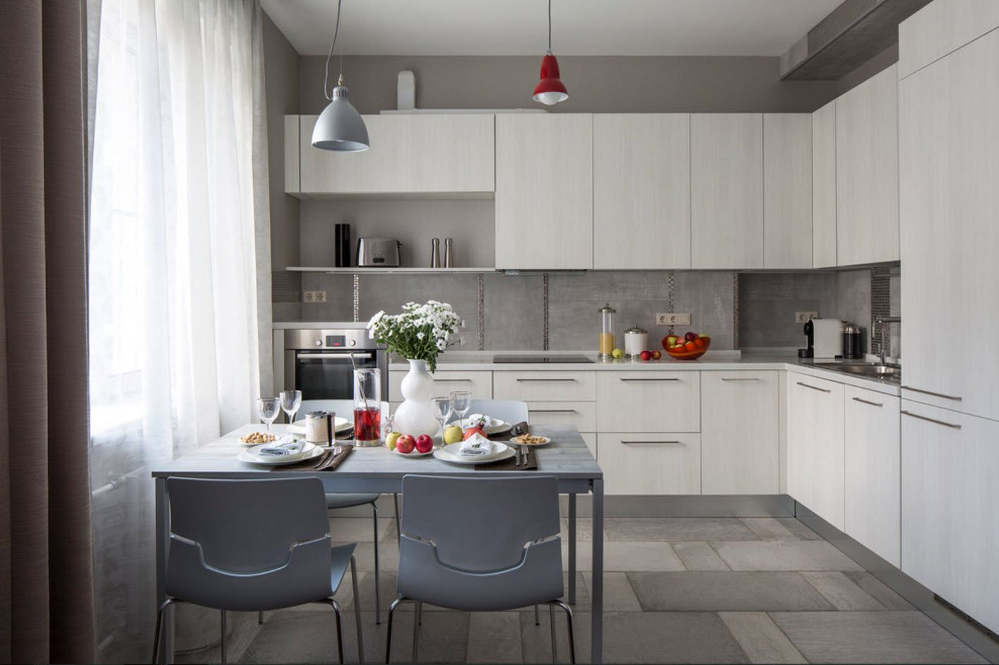 L-shaped kitchen layout with dining group for four persons with plastic gray chairs