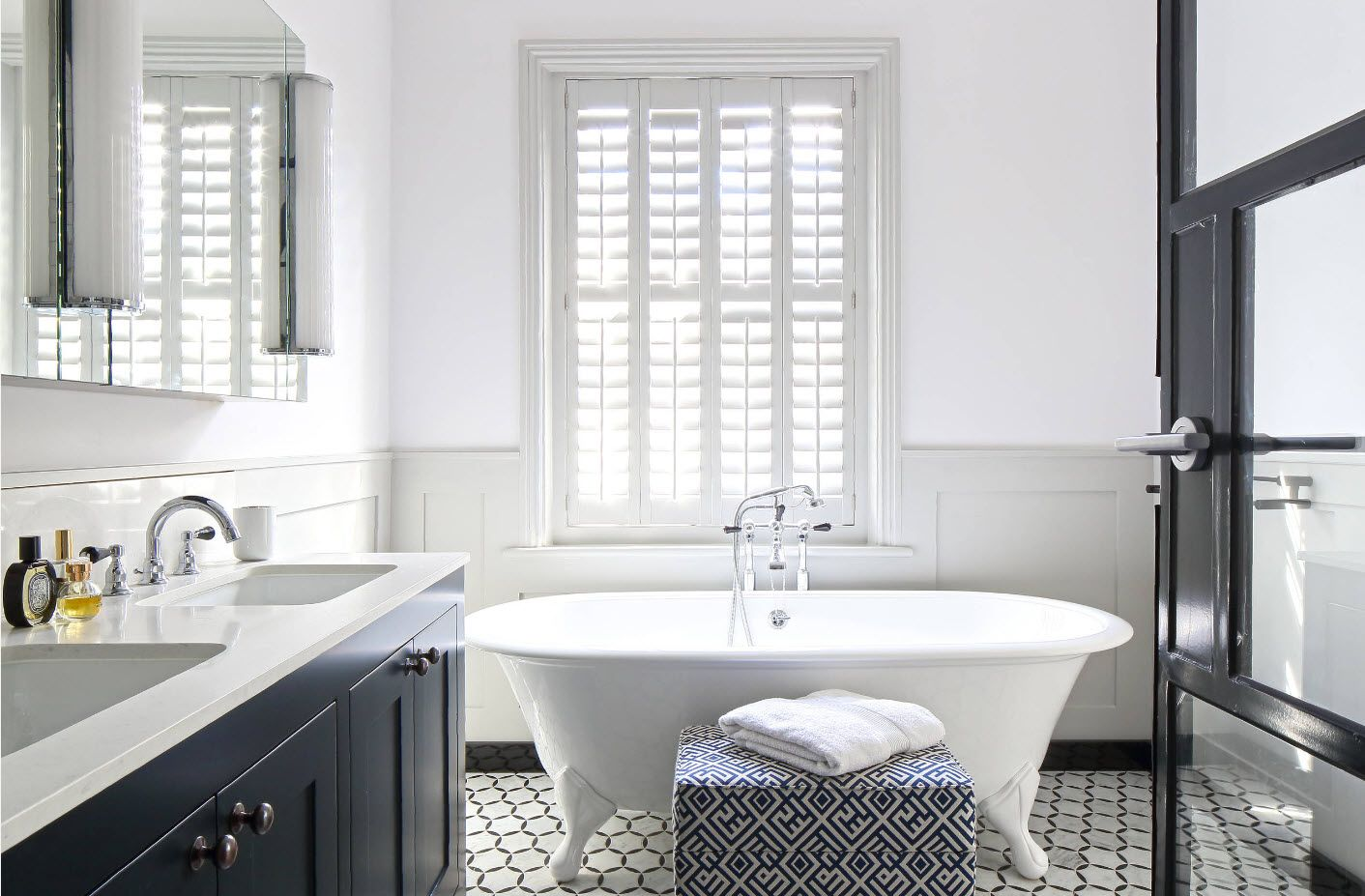 Classic bathtub form and Roman blinds in the white interior