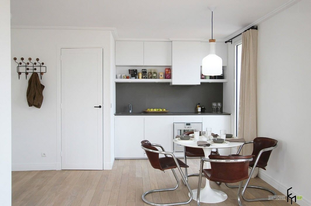French Interior Traditions in Modern Apartment Interpretation. White hi-tech arranged dining zone with plastic chairs at the kitchen