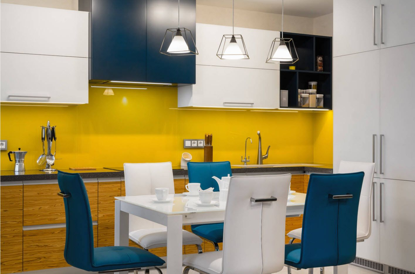 Yellow backsplash of the deep blue kitchen set and blue chairs at the modern cottage