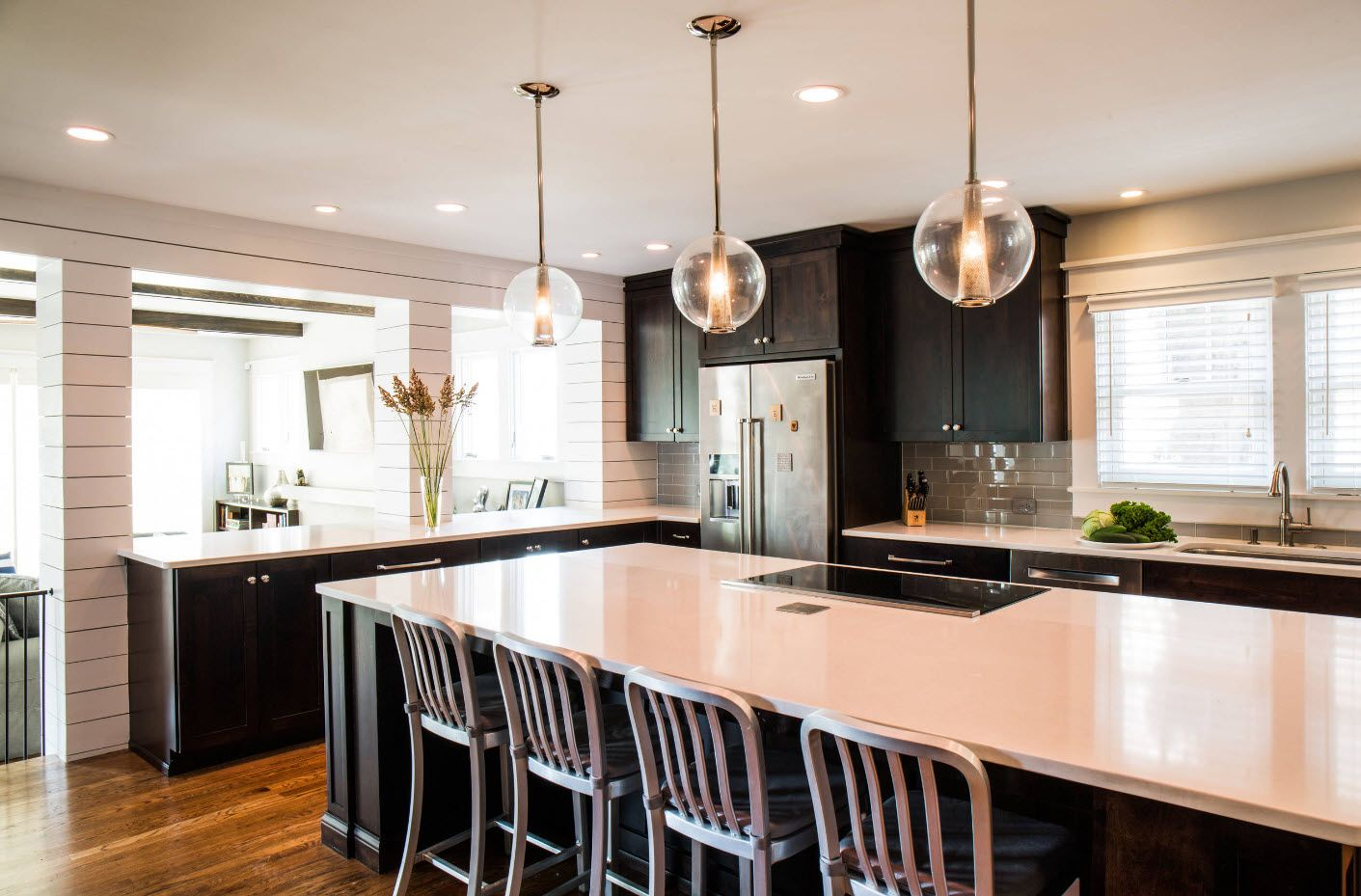 Dining zone at the large multifunctional zone of the kitchen with white matted ceiling and glossy countertop in modern style
