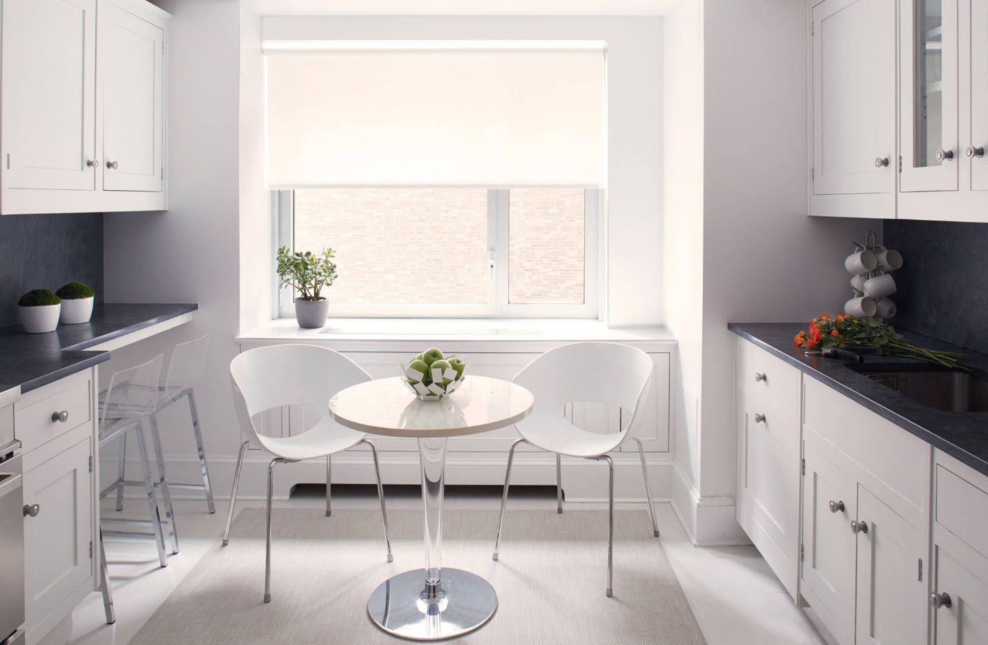White interior of the kitchen with dining group for two and round table