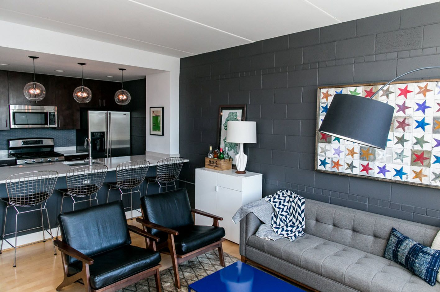 Dark gray accent wall at the modern designed living room with dark upholstered furniture