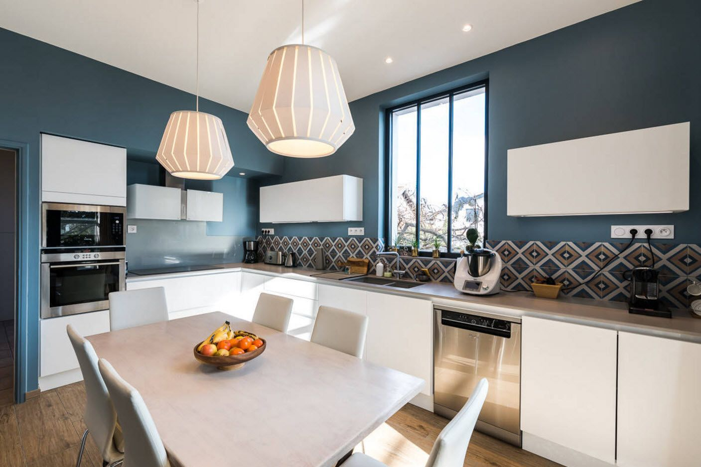 Nice dark blue wall paint decoration in the modern minimalsitic kitchen with large table
