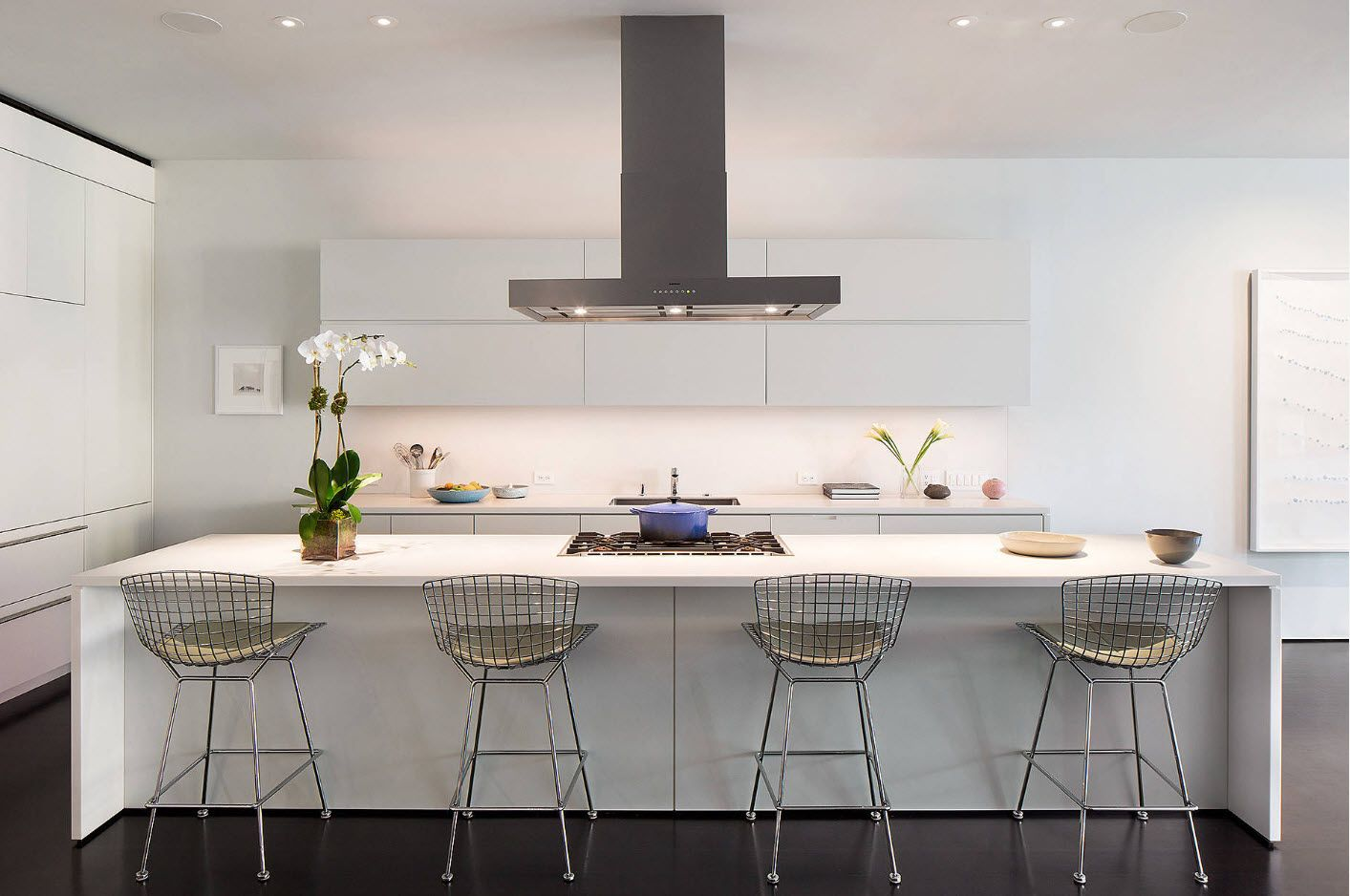 Low hi-tech extractor hood with built-in lighting and neat white kitchen atmosphere with metal framed stools
