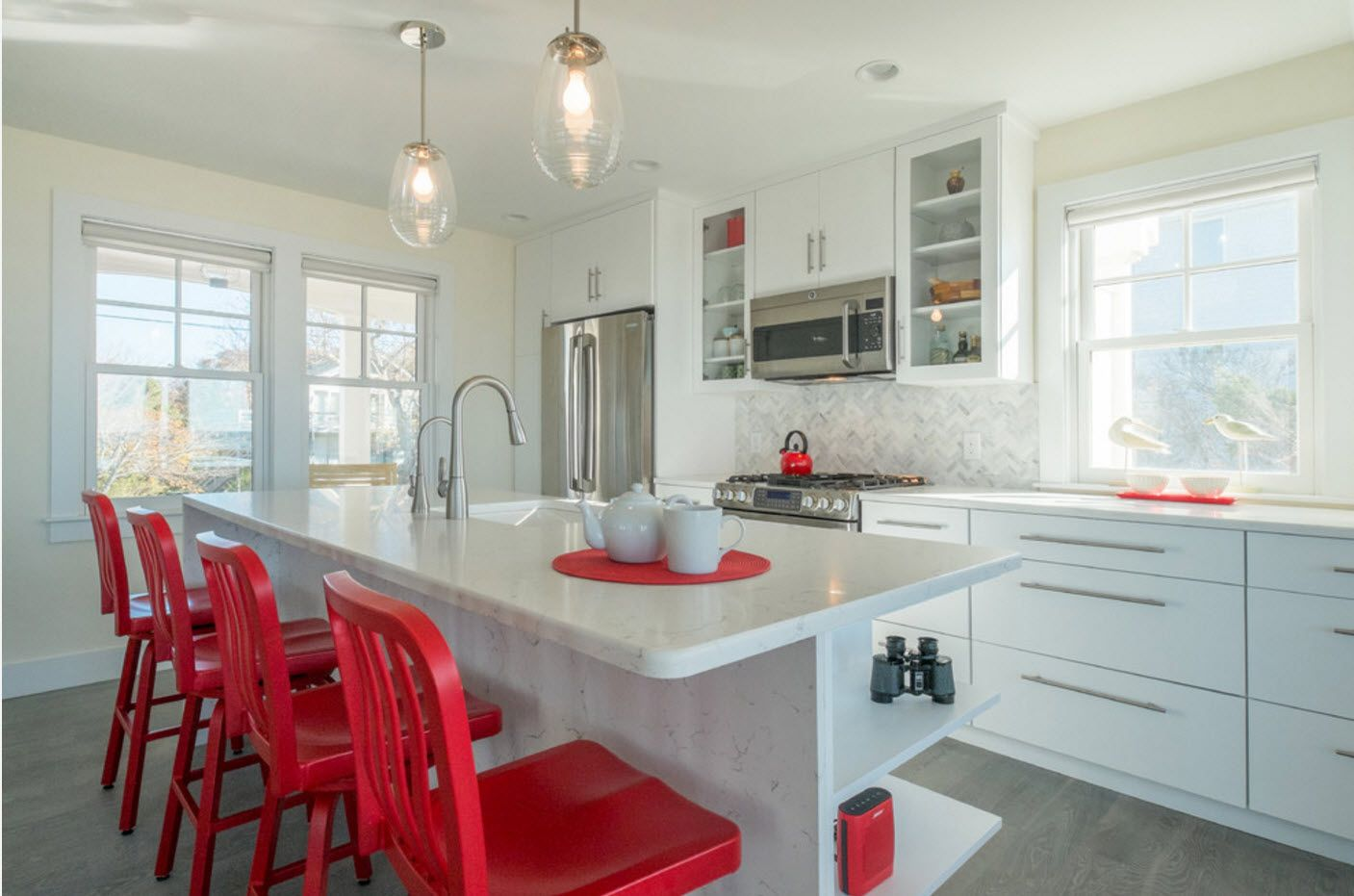 White kitchen deisgn with bright orange accent in the form of chairs and tray