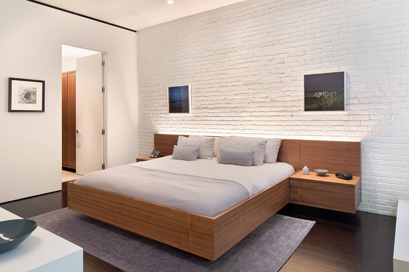 Suspended wooden framed bed and nightstand along with textured whitewashed brickwork creates an amazingly relaxing atmosphere in the bedroom