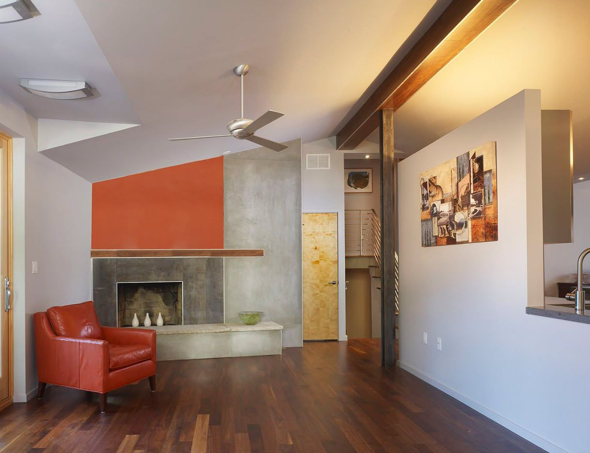 Orange accents in the spacious living room with oak laminated floor