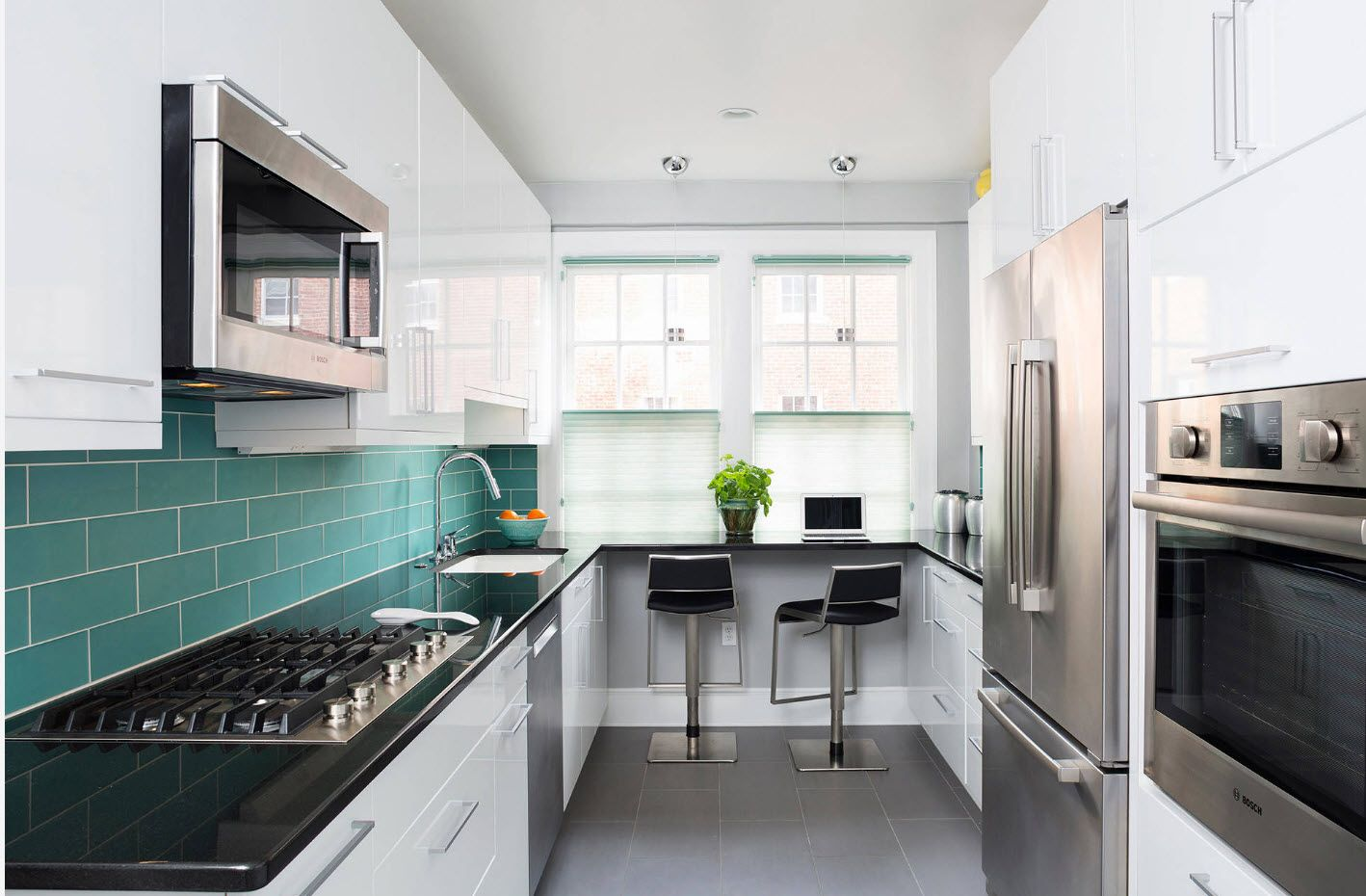 Galley kitchen with dining group and steel surfaces of appliances