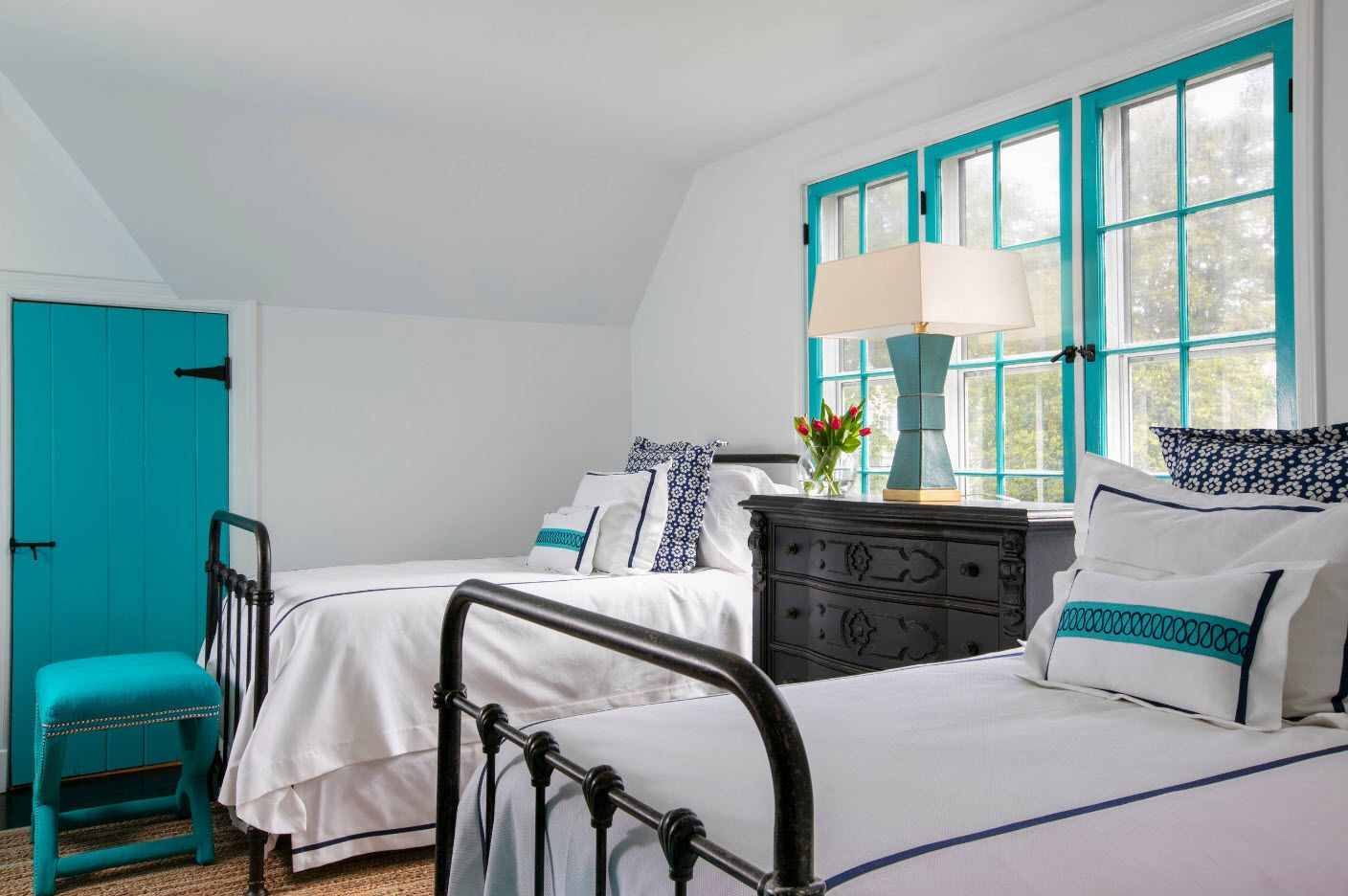 Bright turquoise window frame and two beds with classic chest between them