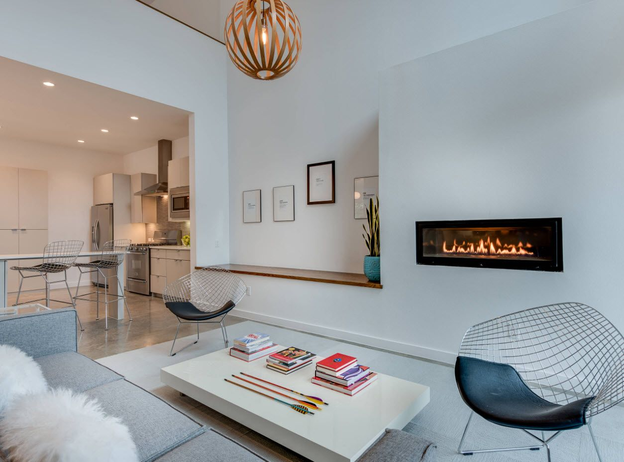 Modern styled living room in the private house in white color palette and fireplace