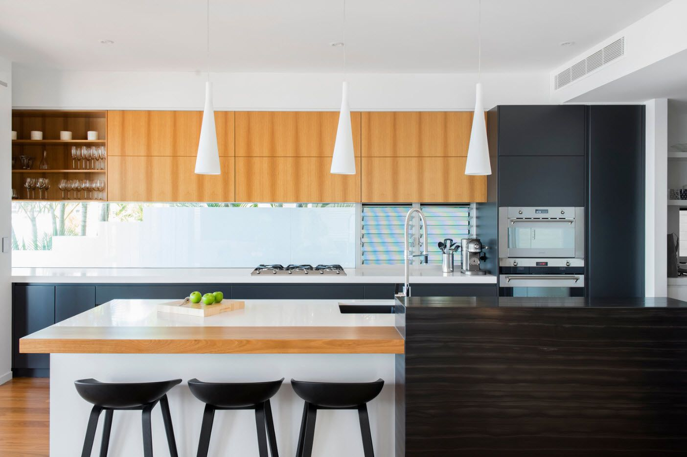 Neat geometrically right formed kitchen interior in modern style with matted lampshades over the dining group