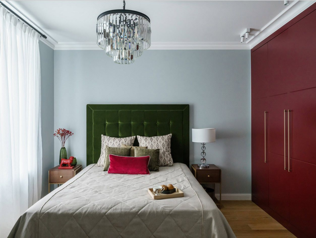 Nice crystal chandelier as an accent in the modern cottage bedroom with dark doors of wardrobe