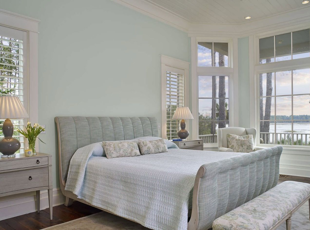 Pale turquoise wall paint at the cottage bedroom with king size bed