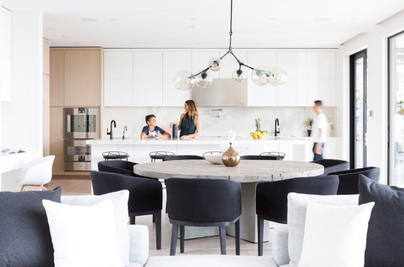 Dining zone with modular armchairs and gray round table at the first floor of the cottage