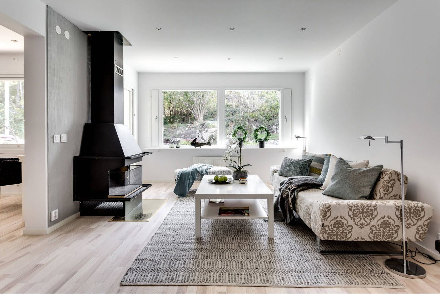 Atmosphere of calmness and dignity in the white living room with black real fireplace with chimney