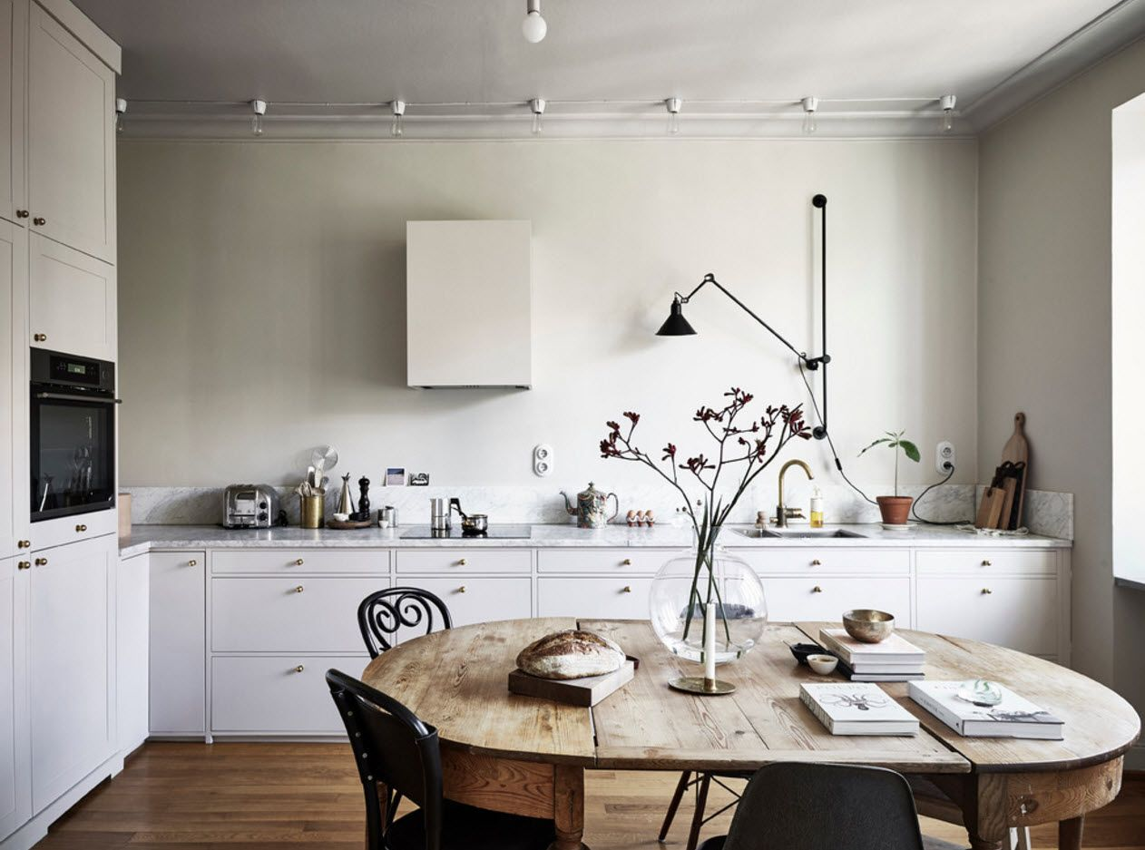 Nice mix of styles in minimalsitic alternatively decorated kitchen with round wooden table