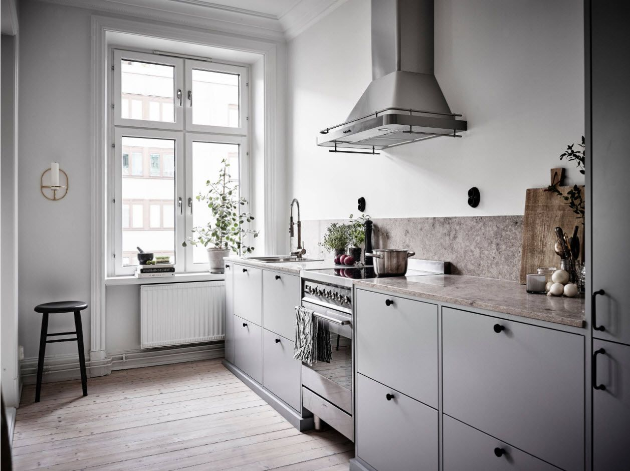 Row layout of the galley kitchen with steel hob and extractor hood and classic bottom furniture set with tabletop