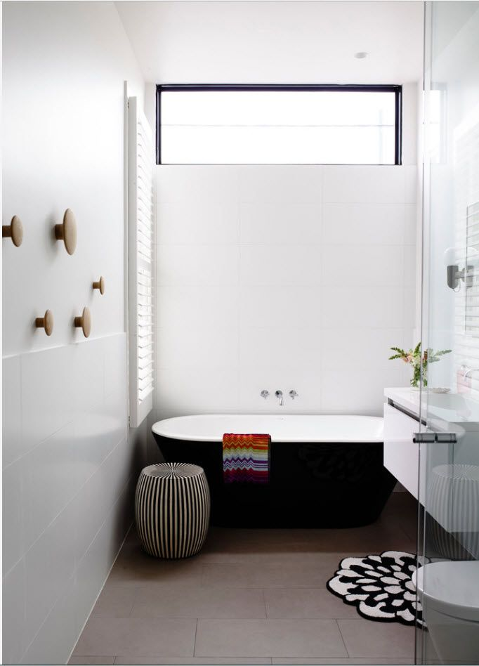 White atmosphere of the modern bathroom with dark side trimming of the bathtub