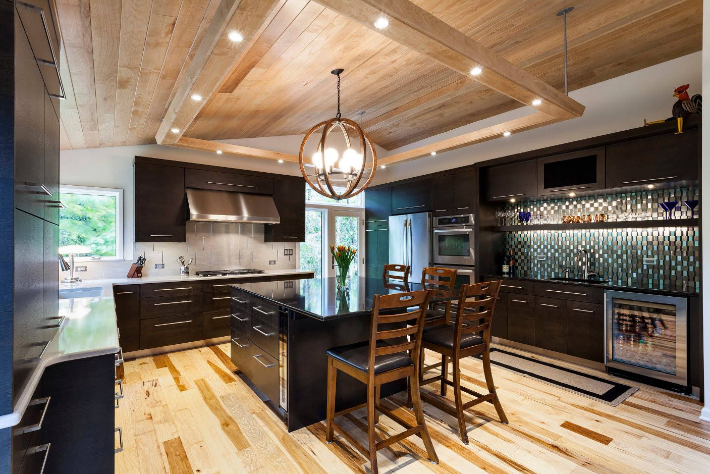 Nice color mix of the light wooden ceiling and florr and dark kitchen set furniture facades