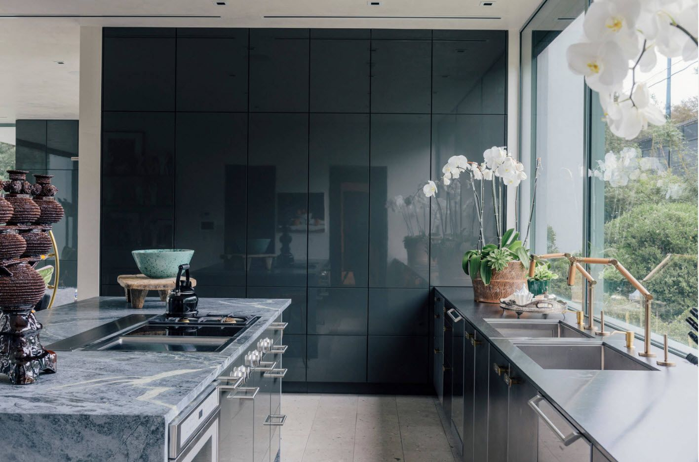 Reflecting glossy dark surfaces of the ceiling-height kitchen set