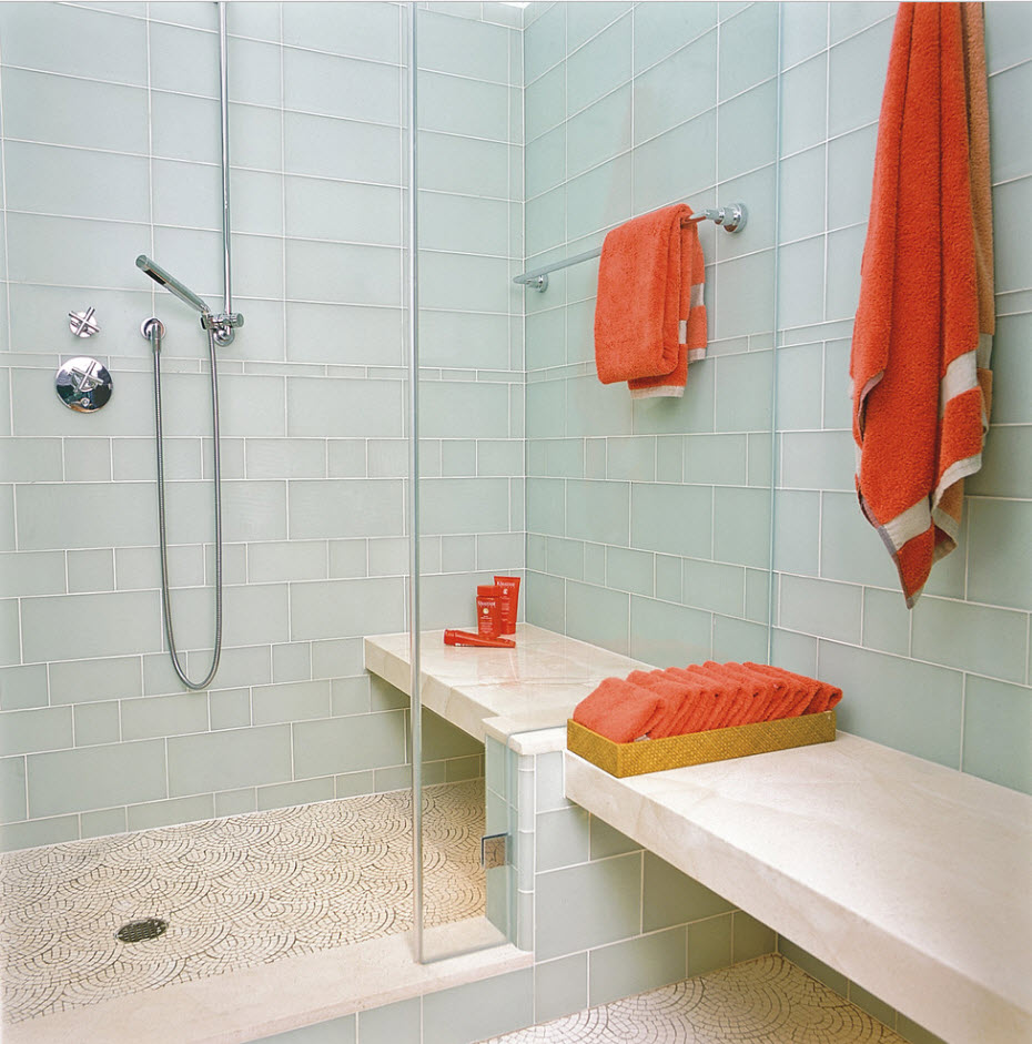 Red accents of towels on the pale blue tiles shower zone