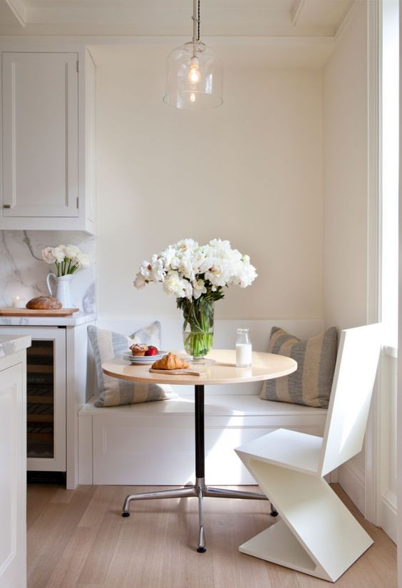 Round small table and the vase with lushy flower at the classic styled kitchen in white