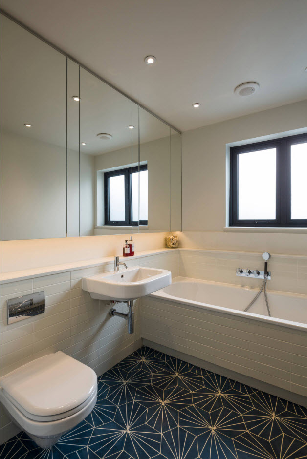 Large contemporary styled bathroom with large mirror, strict forms and dark tiled floor