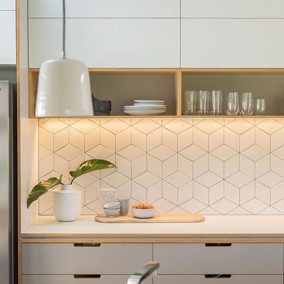 Warm artificial lighting at the modern kitchen with rhombed splashback zone