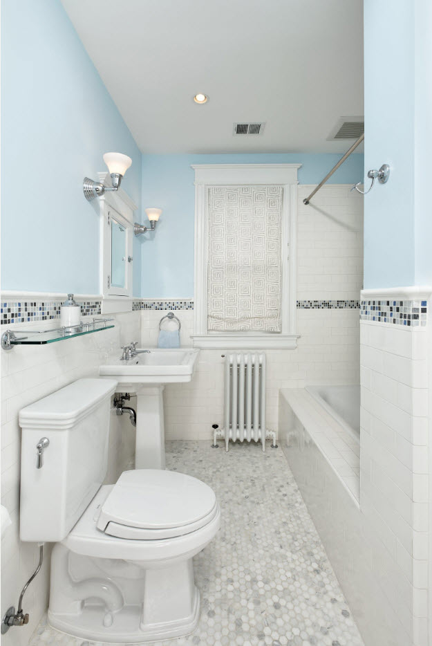 Neat blue top of the wall and white tiled bottom part with mosaic line between