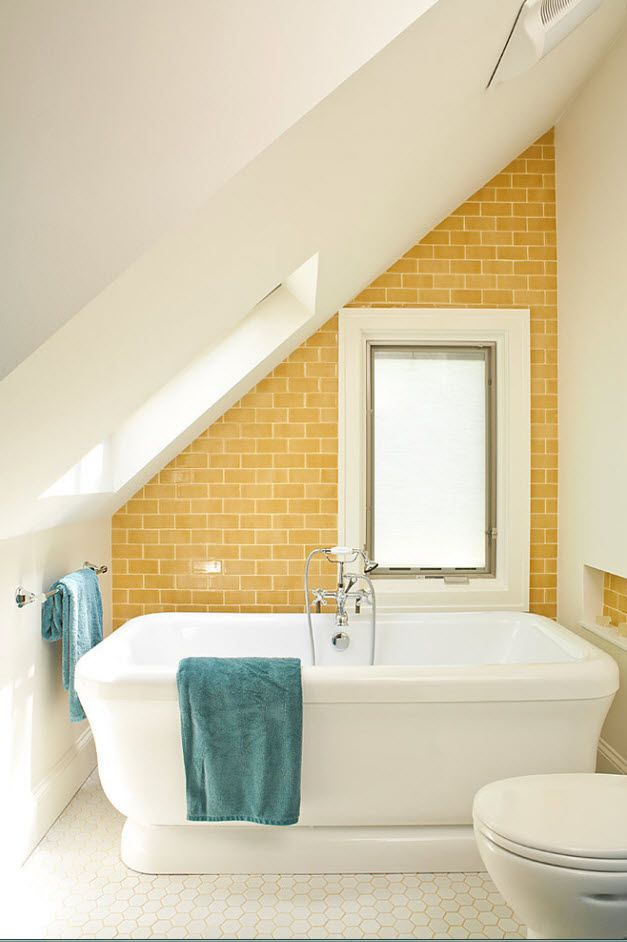 Loft bathroom with abrupt slant of the ceiling and yellow small square tile and whitewashed seams