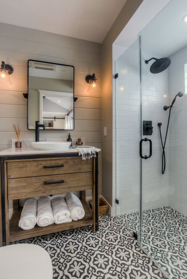 Dark metall plumbing in the glass partitioned shower zone and wooden vanity with towels