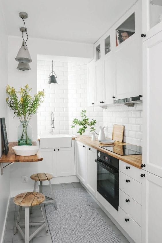White Scandinavian design style at the kitchen with island dining zone and plants