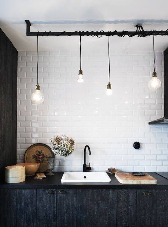 Black cords of bulbs and wall, tabletop at he background of the white textured with tiles wall in the modern minimalsitic contrasting kitchen