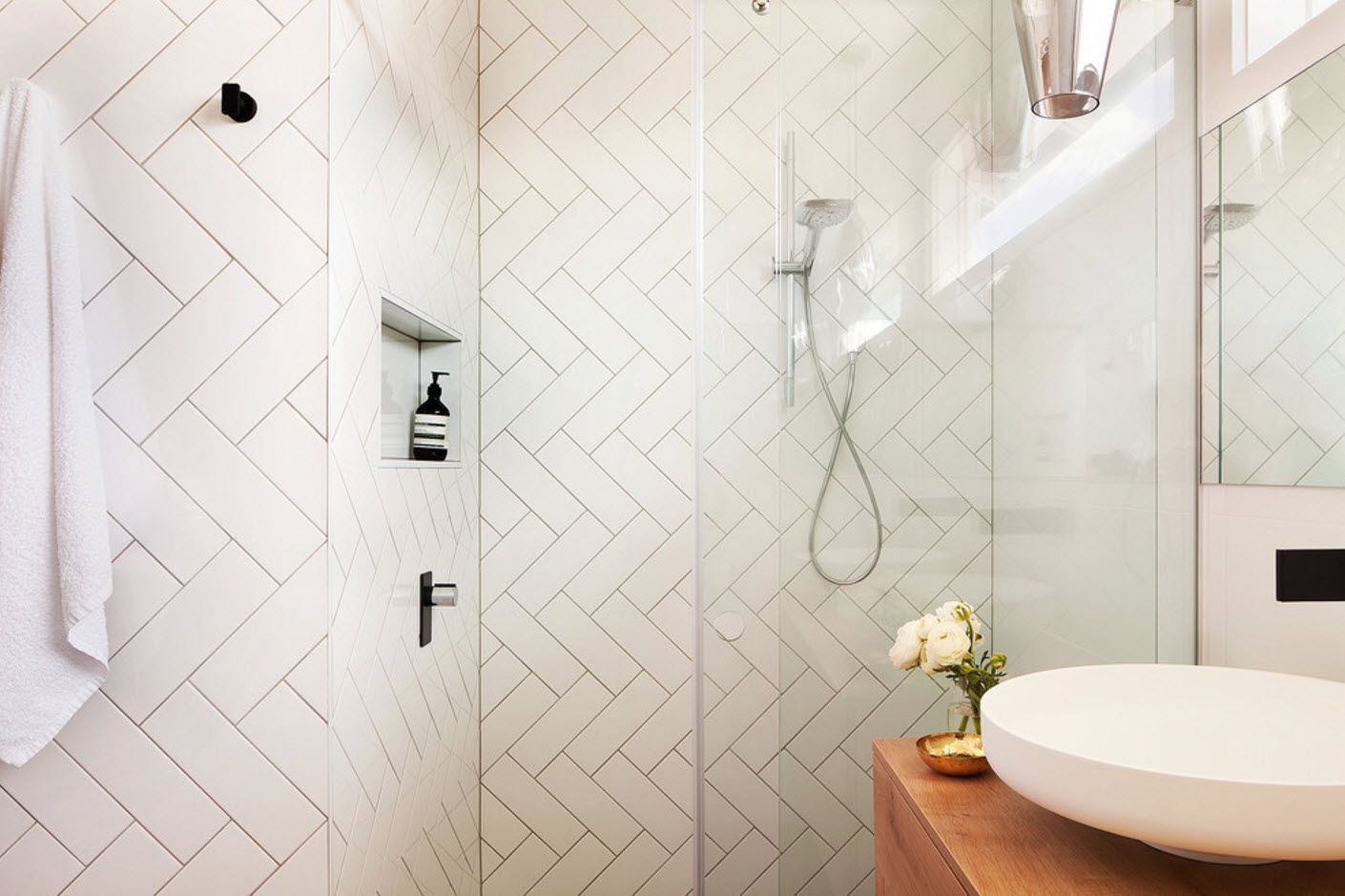 Herringbone prolonged tiles of the shower zone and minimalistic arrangement in the bathroom