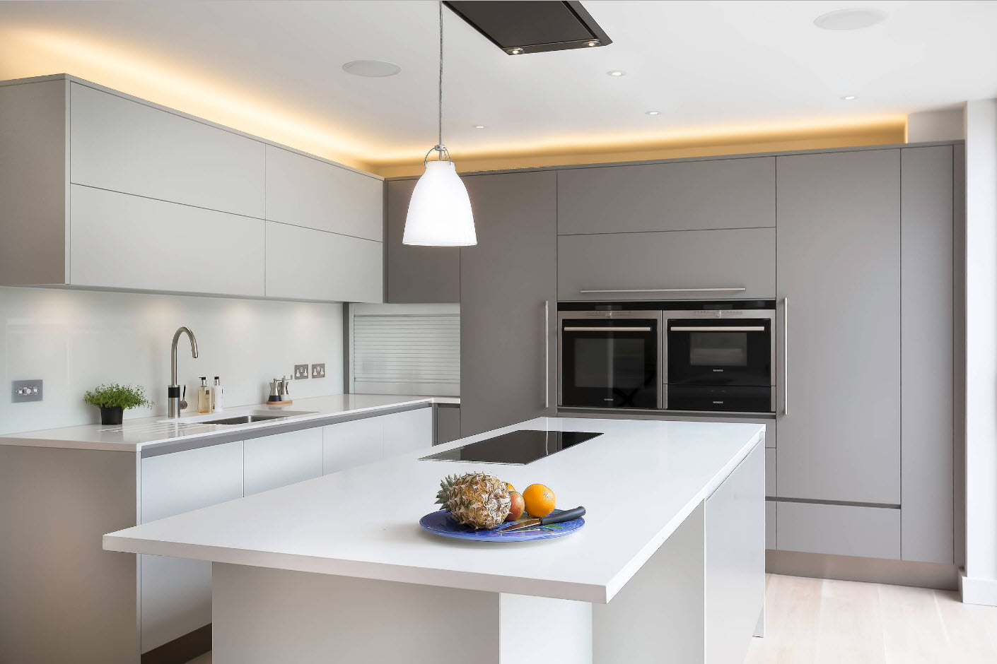 Gray minimalsitic kitchen furniture and solid white splashback
