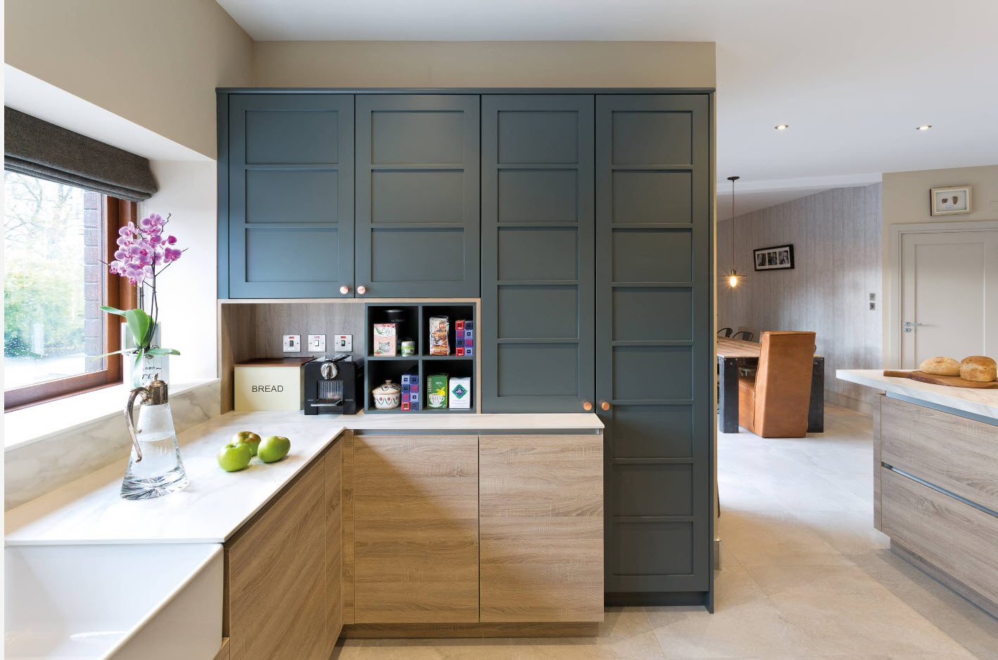 Dark plasticine furniture surfaces and laminated bottom tier storage in the modern styled kitchen