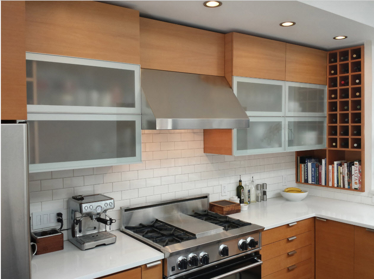 Wooden top tier surfaces of the kitchen set and matted glass windows of drawer with aluminum frames