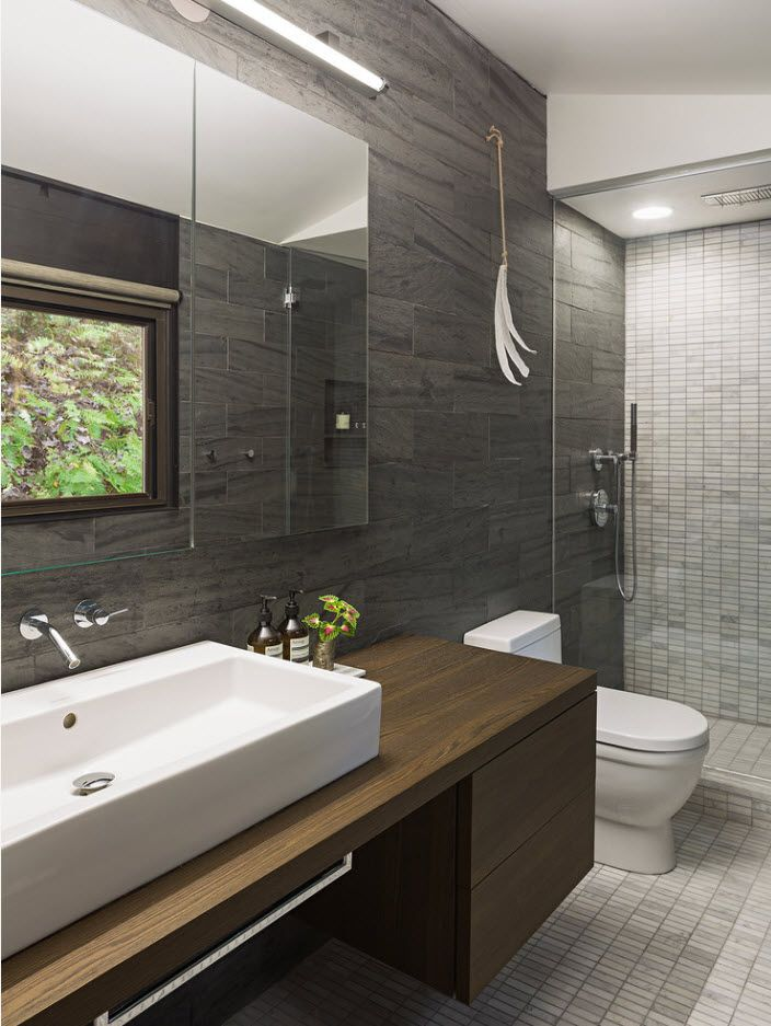 Graphite gray tiling of the modern styled bathroom