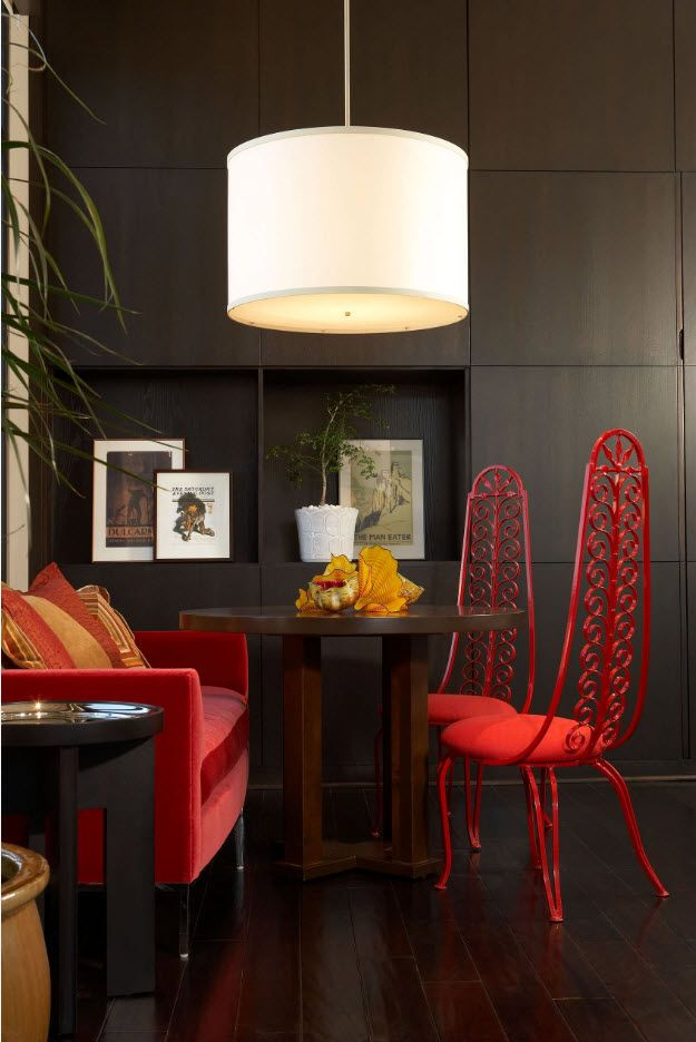 Orange contrasting chairs in the dark entourage of the dining