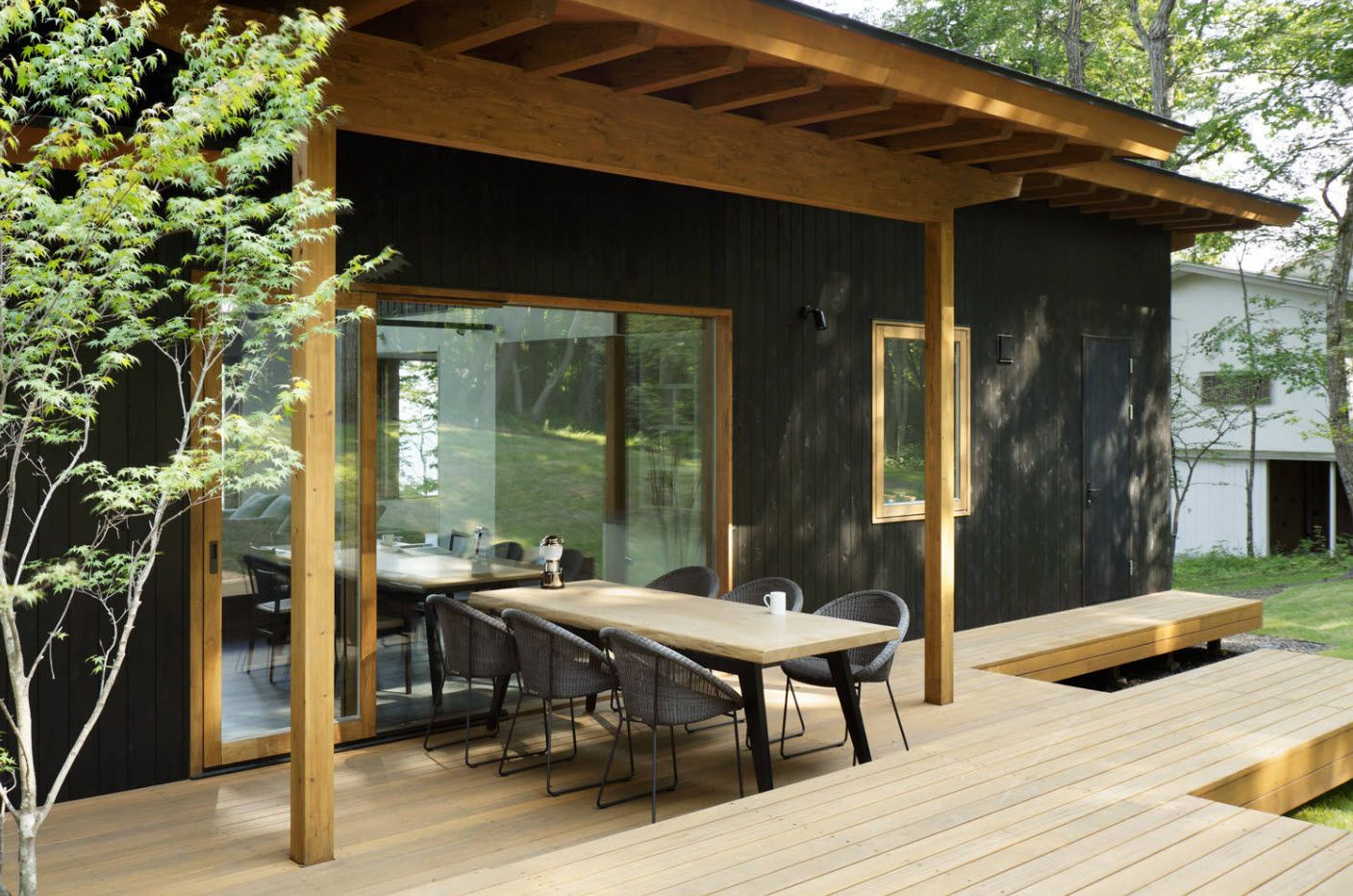 Experimental and spectacular design of the open terrace at the porch with black house facade and light wooden platform and roof