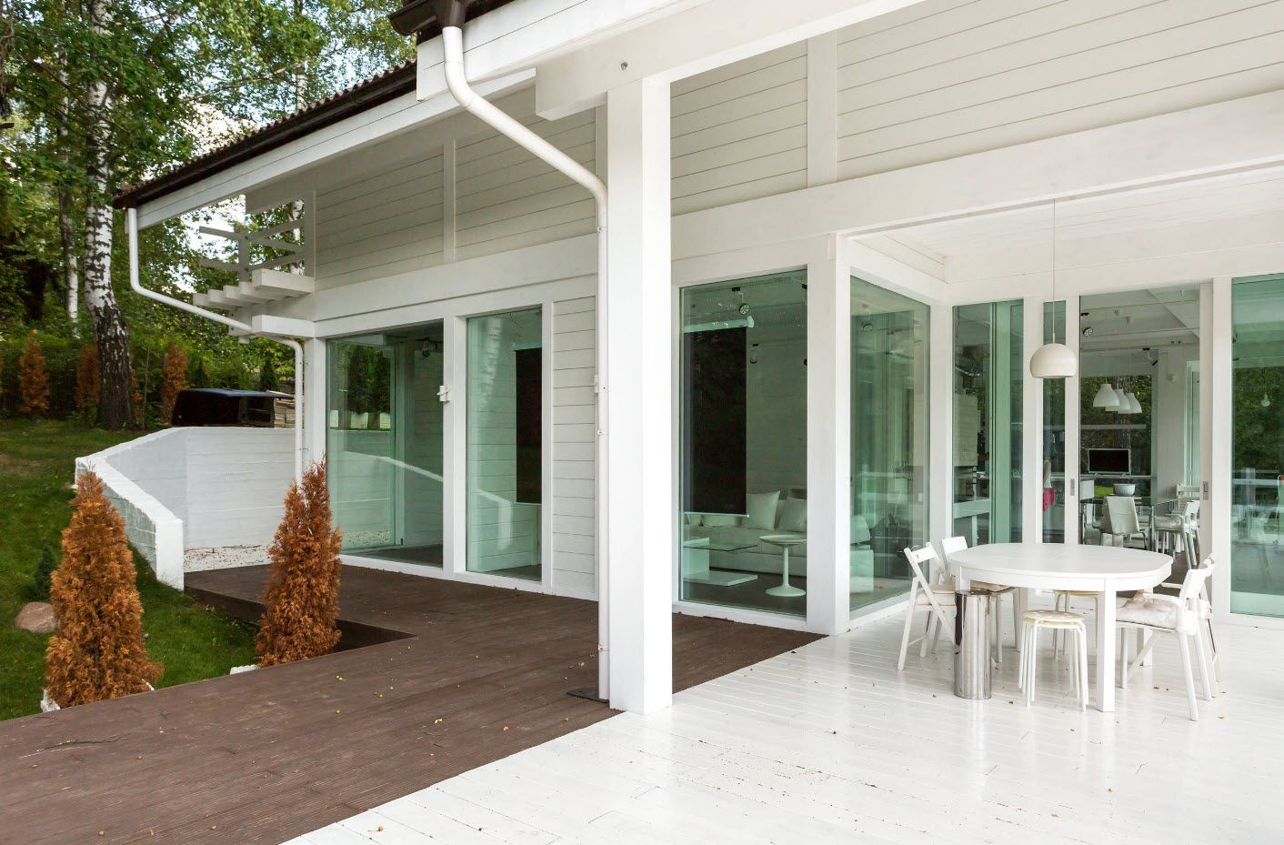 Spectacular white house facade, wooden pathway and glass panoramic windows